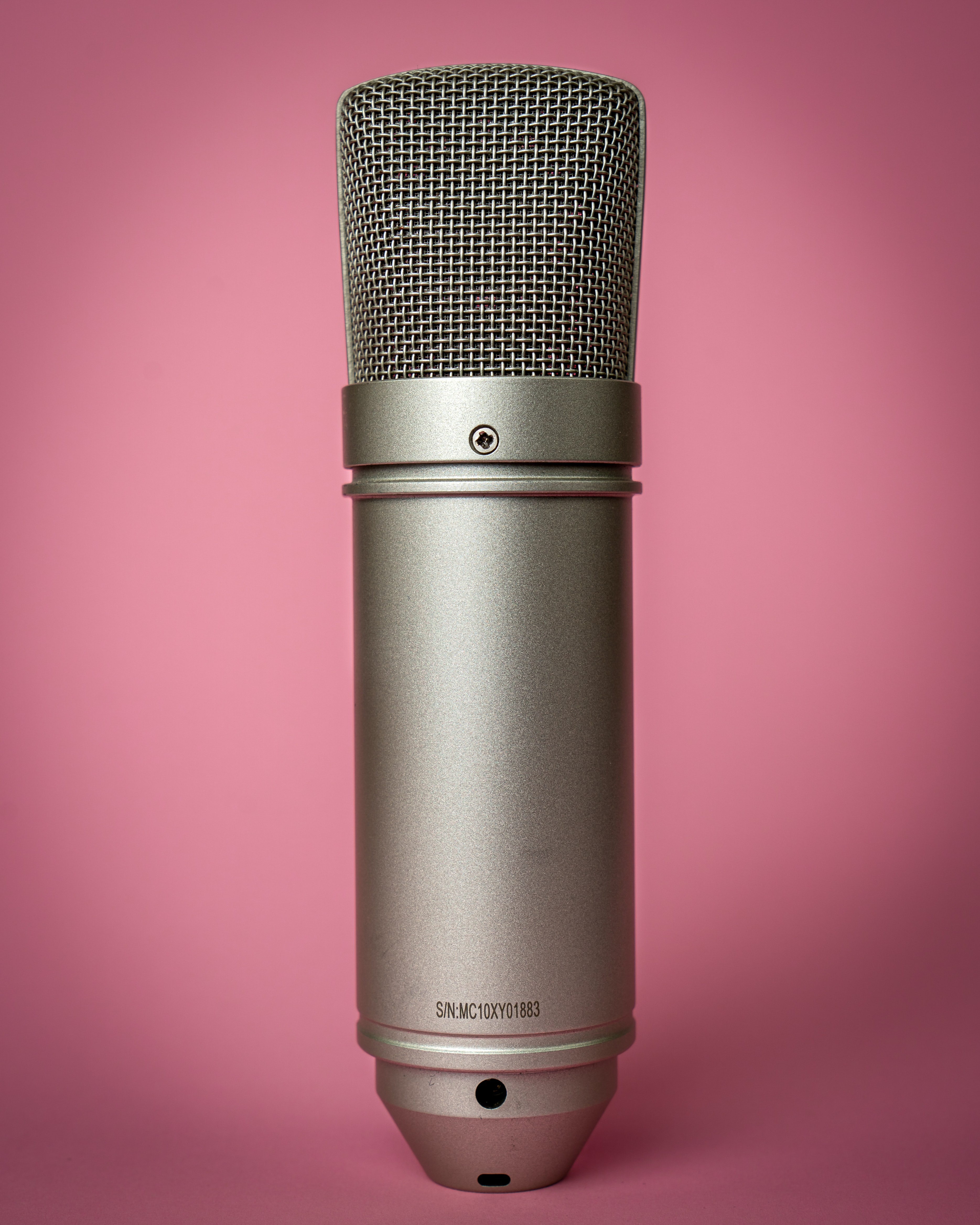 Large Condenser Microphone majestically set against a soft pink background.